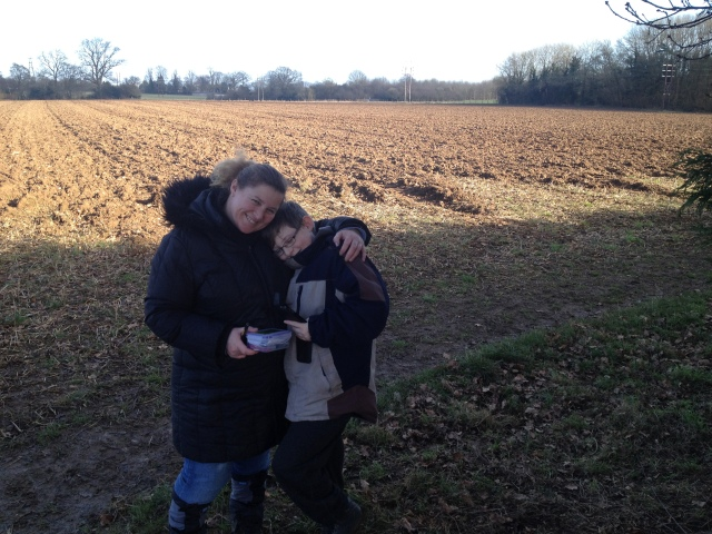 Sam and Shar hug as they stand at the GZ of Plimsaul's Haul with an open field in the background behind them