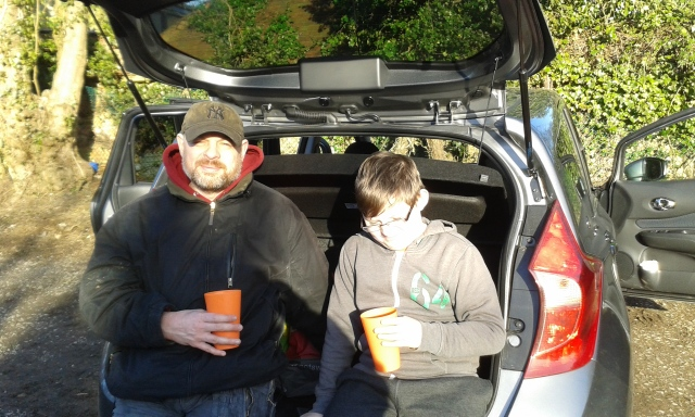 Sam and Paul sit in the boot of the car drinking hot chocolate. The sun shines on their faces