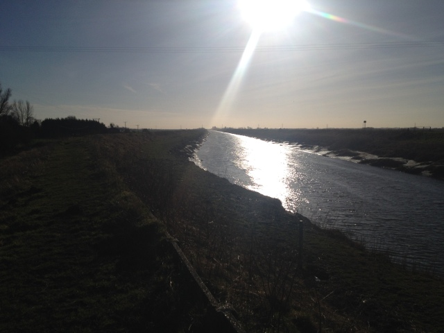 This picture is taken into the sun along the river near Denver Sluices causing the light to diffuse the detail in the picure and reflect off the surface of the water