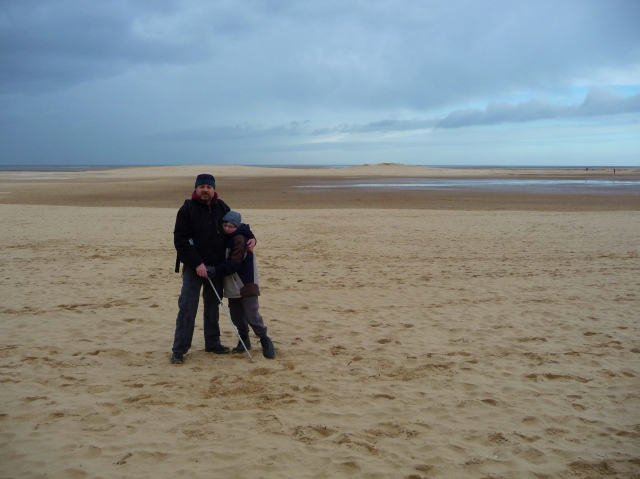 Sam and Paul stand hugging on the beach at Wells. The sand stretches into the distance behind them and the skies are darkening with the threat of rain