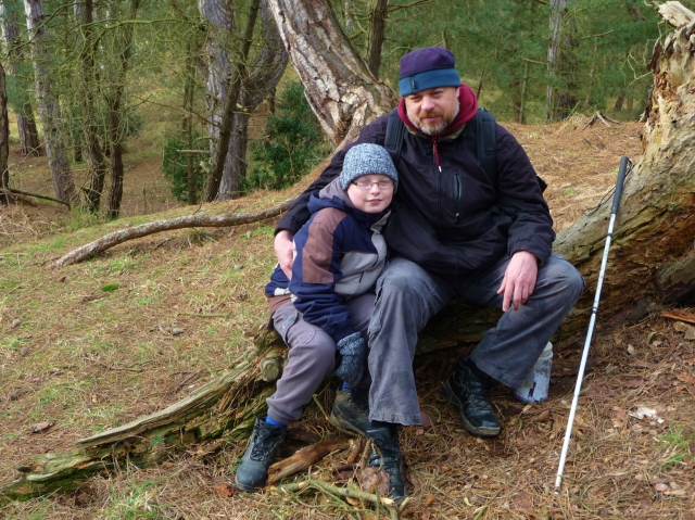Paul and Sam sit on a log at the GZ of one of the caches in Wells Woods