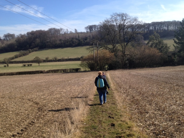 Shar and Sam walk down into Chesham Vale. The path down doesn't look that steep but beyond a road in the distance the hill opposite can be seen rising up sharply, the side of it covered in trees.