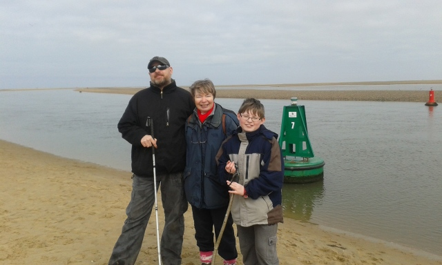 Paul, Sam and Sandra stand next toa beached buoy on the Sand at Wells. The sea has retreated far enough for the buoy to become beached.