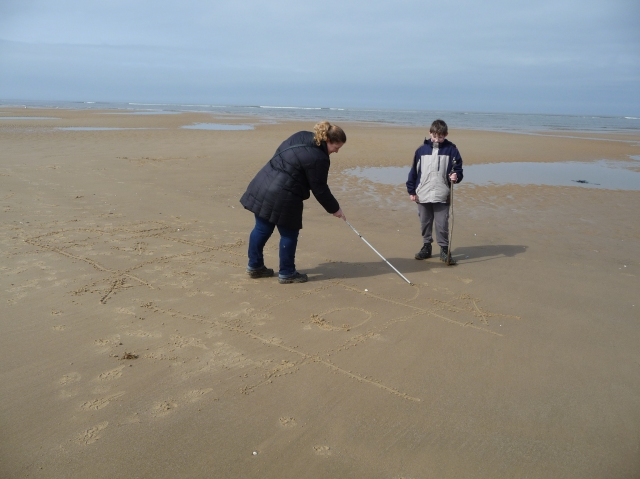 Sam and Shar play noughts and crosses in the damp smooth sand near the waterline on wells beach at low tide.