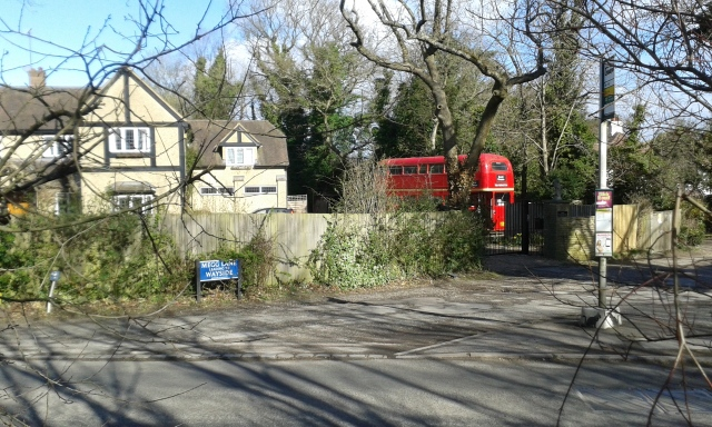 A double decker bus, the type normally found in London about 20 years ago is parked in a driveway in Chipperfield