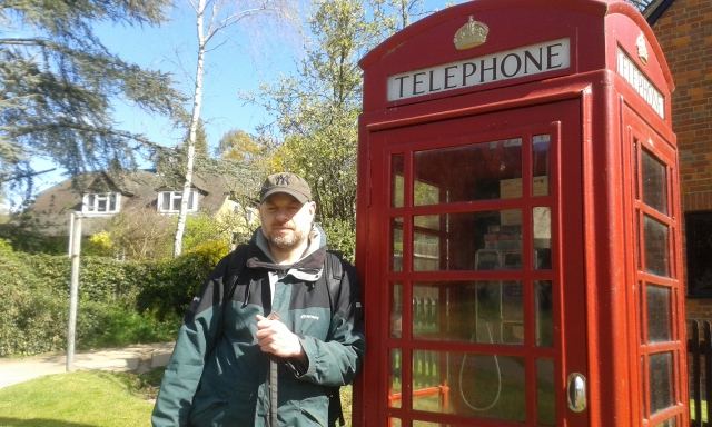 Paul is pictured standing outside an old red phonebox in Belsize