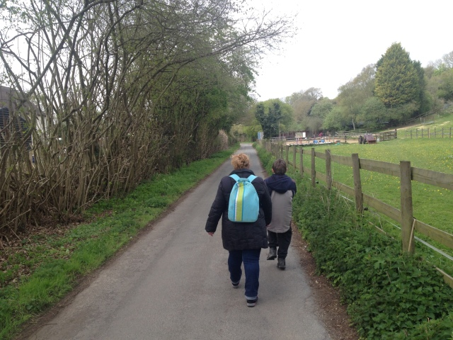 Sam and Shar walk away from the camera along a narrow country lane that winds into the distance