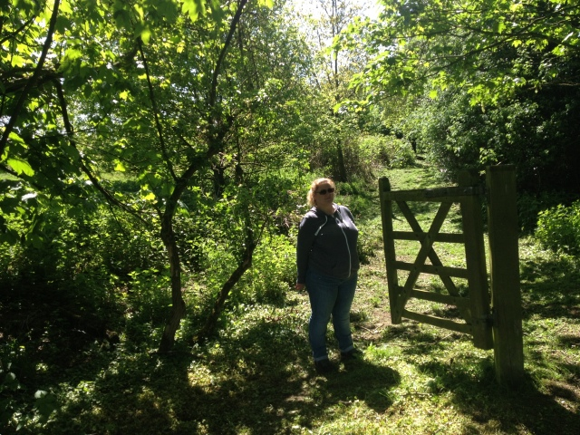 Shar stands in the shade of the trees next to half a kissing gate that is open on all sides. There is no fence.