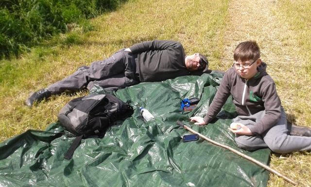 Paul lies on a groundsheet that has been placed at the side of an open field. Sam sits on the groundsheet eating an apple.