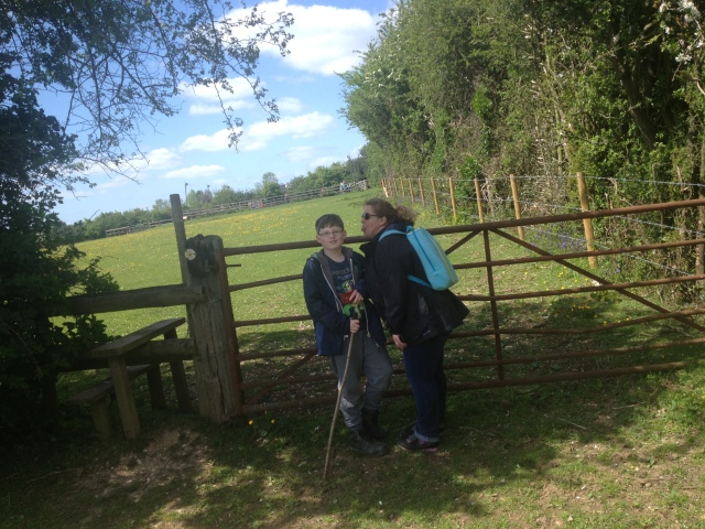 Sam and Shar stand in front of a wide field gate. Shar pokes her tongue out mokingly at Sam