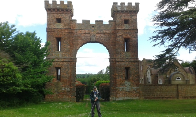 Paul stands under a huge brick arch. The corners of the archway are crenulated like castle turrets.