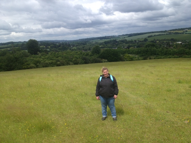 Shar stands with her back to a wide open view of Hertfordshire countryside.