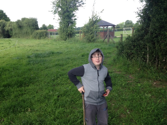 Sam poses holding his trackable stick in a field. His hood is up despite it being june.
