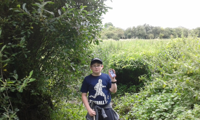 Sam stands at the tree within a tree with the lush vegetation of the water meadow visible in the background
