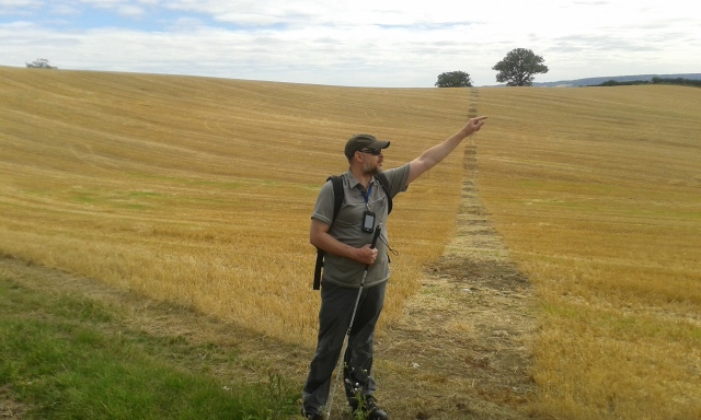 Paul stands in a field posing and pointing into teh distance like some sort of catalogue model / idiot