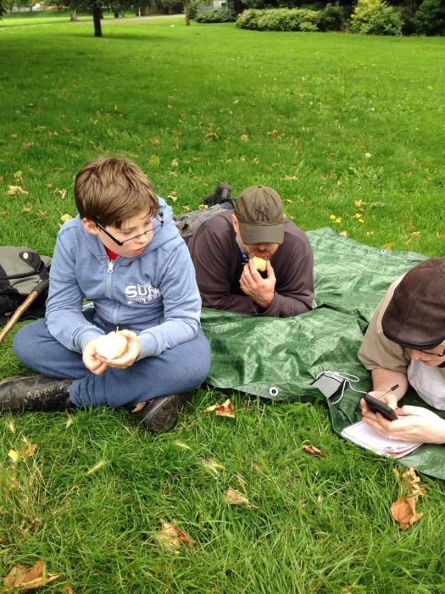 Geoff,  Paul and Sam sit on the groundsheet after lunch trying to solve the puzzle cache.