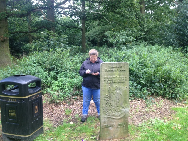 Shar stands behind a wood sculpture of a mouse that holds the sign for Tanner's wood. She is collecting numbers off the information board behind for a multi cache