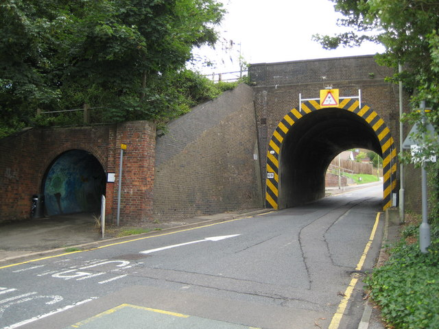 This photo shows a brick narrow arched bridge with the train passing over the top and the road going underneath. The road is narrow through the bridge and a separate pedestrian tunnel can be seen to the left of the road tunnel.