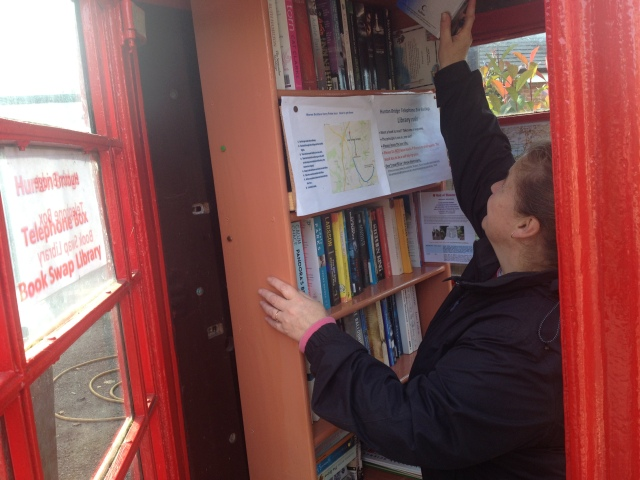 Shar is pictured inside a red telephone box with the door open. The box has been converted into a library and she is selecting a book from the shelves