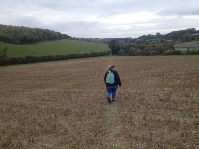 Shar walks away from the camera through fields.