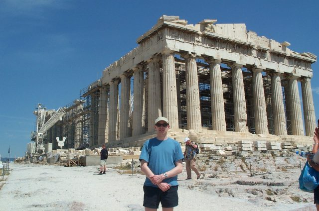 Paul stands in frot of the huge ediface of the parthanon