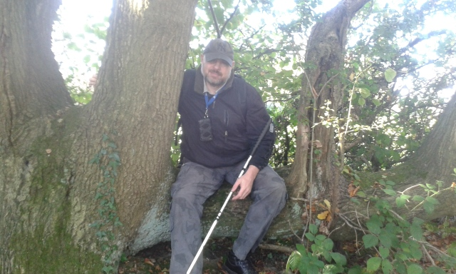 Paul sits on a low extending Tree limb that resembles a seat. He is hugging the tree trunk to his right.
