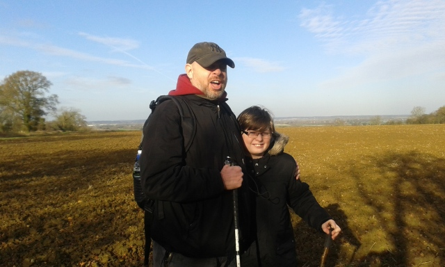 Sam and Paul stand with a ploughed field behind them and a winter scene stretching into the distance beyond. Paul i making a silly face