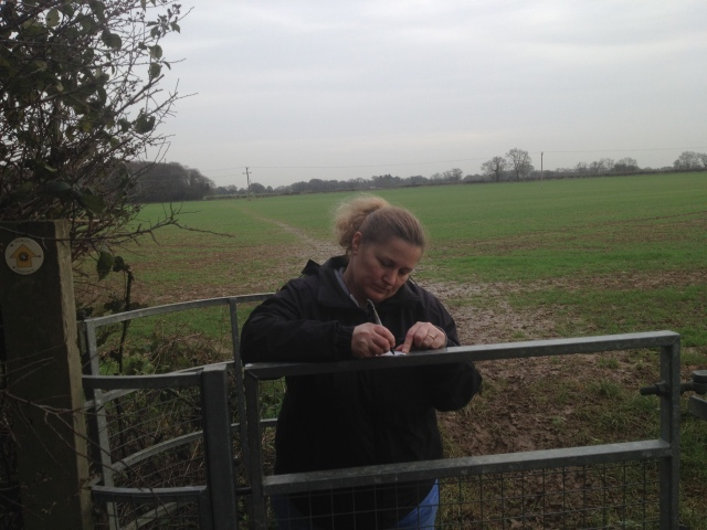 Shar stands singing a log at a cache near a gate with a muddy field in the background