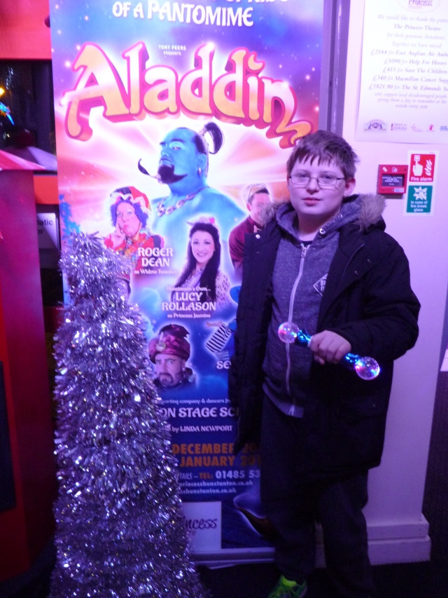 Sam stands in front of a sign advertising Aladdin at the Hunstanton theatre