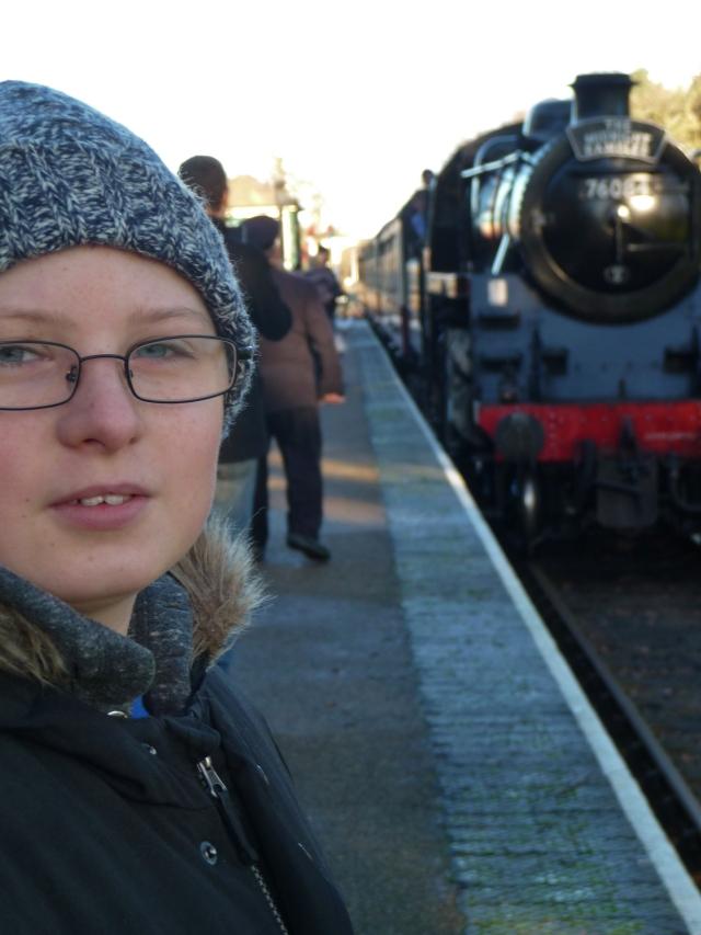 Sam stands on the platform at Holt station as the steam train arrives