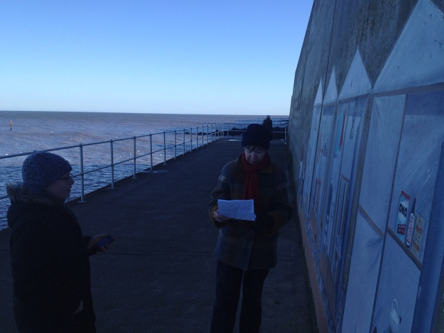 Sandra and Sam sutdy the mural painted on the prom wall to find the information needed to calculate the location of a nearby geocache.
