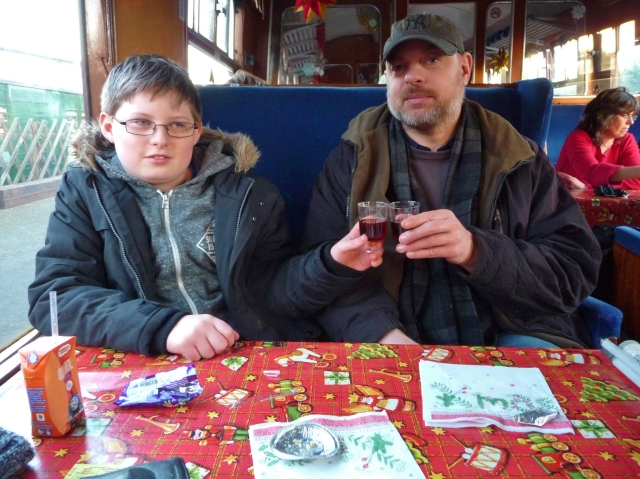 Paul and Sam sit on the train holding plastic sherry glasses, Paul looks somewhat dazed!