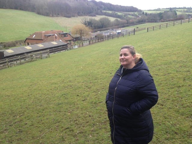 Shar stands on a hill with a view down into the valley behind her. The sky is gloomy