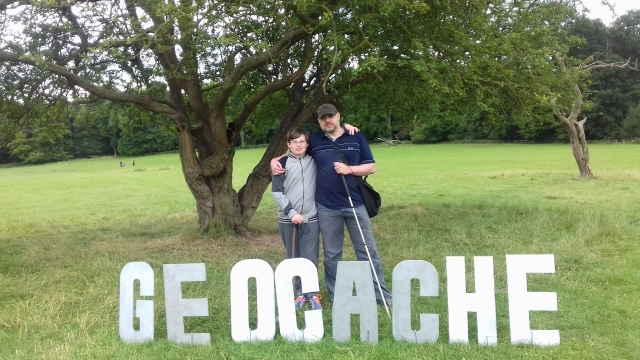 Sam and Paul stand behind a hollywood style sign spelling the word geocache made up of letters approx 12 inches high. Beyond is a tree where the cache was hidden.