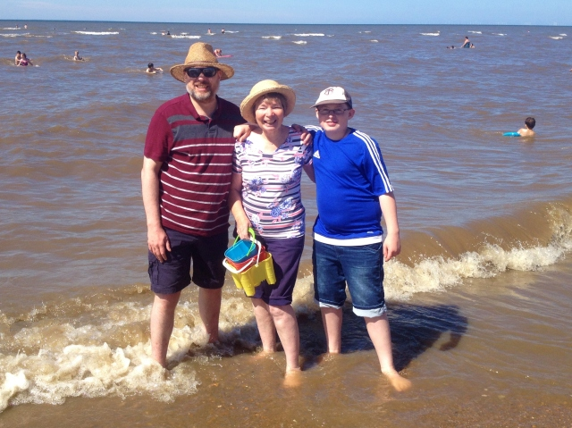 Paul, Sam and Sandra stand ankle deep in the sea.