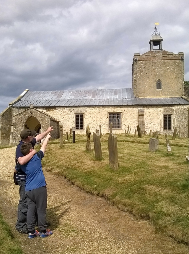 Sam and Paul stand in front of the main entrance to the small church at Burnham Overy pointing up at the building