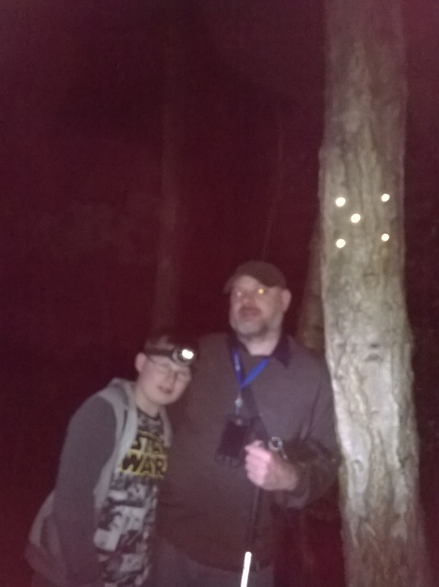 Sam and Paul stand next to a tree that has an X marked out in reflective tacks. It is very dark