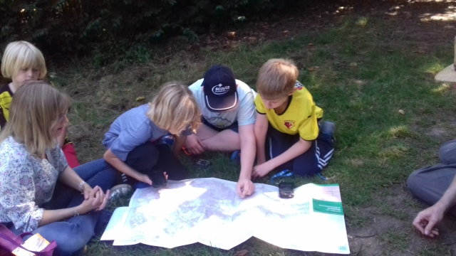 Jo and the boys are seated on the ground around an unfolded Ordanance Survey map