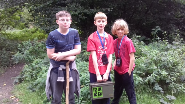 Sam Ben and Ethan pose on a path in the woods holding the ammo can geocache