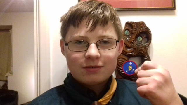 Sam stands holding his scouts geocaching badge