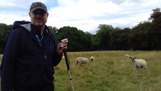 Paul stands in a field holding the Jimmy Talon TB while a sheep looks on.