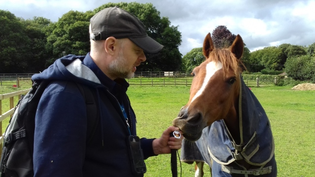 Paul stands in a field next to a horse holding his Jimmy Talon TB. The horse is just about to nibble the TB and possibly Paul's fingers.