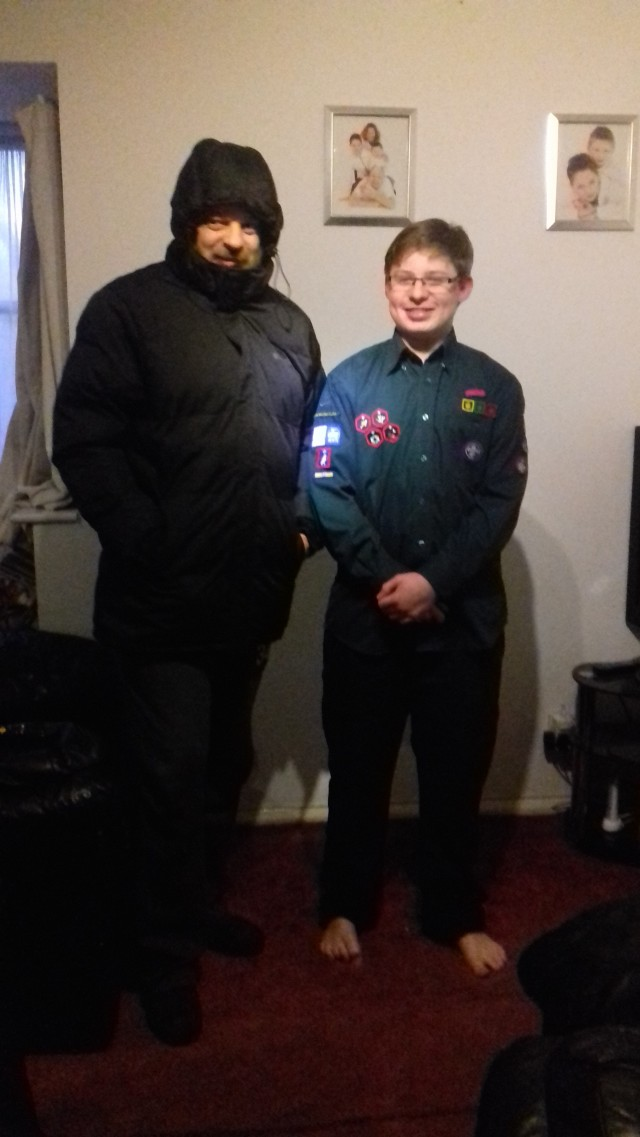 Paul and Sam stand inside at home wearing their prizes. Paul has a winter coat button up all the way with his hood up and is also wearing slippers. Sam wears his scout uniform and a pair of cool outdoor lined trousers. The are both somewhat comical figures ready for the outdoors standing inside.