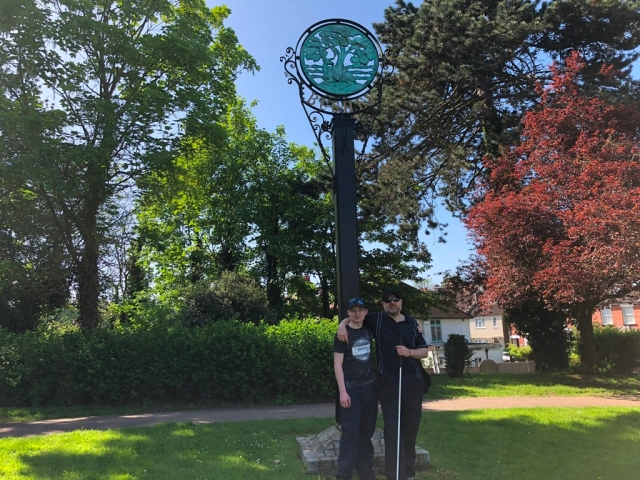 Paul and Sam stand in front of the Bushey village sign